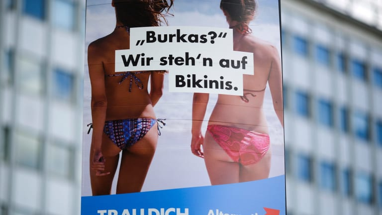 """An election campaign poster of the German nationalist anti-migrant party AfD, Alternative for Germany, reading """"Burkas? We like bikinis."""" is displayed in Berlin."""
