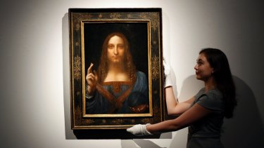 An employee poses with Leonardo da Vinci's 'Salvator Mundi'.