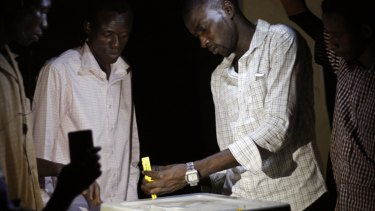 Election officials count votes by flashlight in a school used as a polling station in Niamey on Sunday.