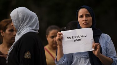 "A woman in Ripoll holds a placard stating in Catalan ""not in my name""."