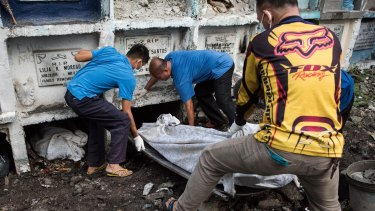 Morgue workers carry an unclaimed body and victim of an extrajudicial killing to a grave in Manila.