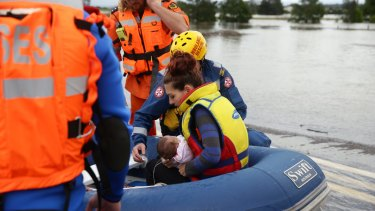 A young mother and her seriously ill four-month old baby are taken across the flooded Cessnock Road in an inflatable boat.