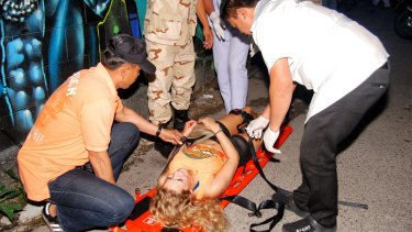 Rescue workers help an unidentified woman after a bomb blast in  Hua Hin on Thursday.