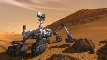 In this 2011 artist's rendering provided by NASA/JPL-Caltech, the Mars science laboratory Curiosity examines a rock on Mars.
