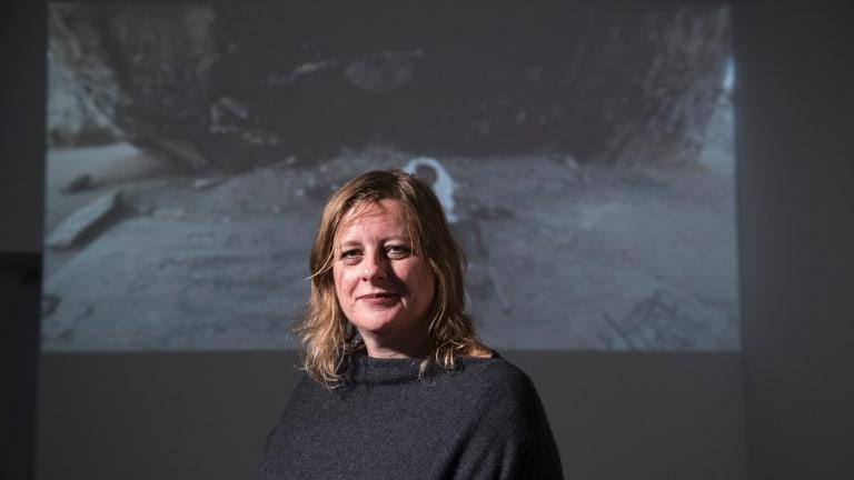 Blake Prize 2018 winner Tina Havelock Stevens in front of her six-minute video <i>Giant Rock</I>.