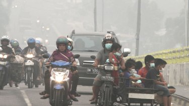 Motorists ride on a road as thick haze from wildfires blankets the city of Pekanbaru, Riau province.