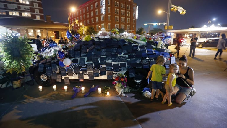 People visit police cars decorated as a public memorial in front of Dallas police headquarters.