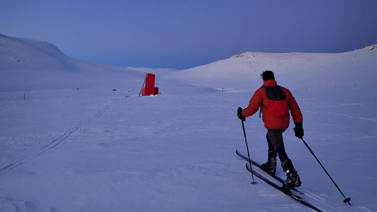 Charlie Freer cross country skis towards Cootapatamba Hut in the gloaming just after sunset.