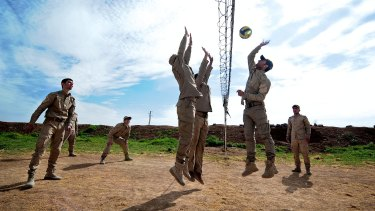 New conscripts to Rojava's army play volleyball during a break from training at an abandoned Syrian military base near Ramalan.