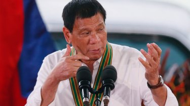 Philippine President Rodrigo Duterte gestures with a firing stance.