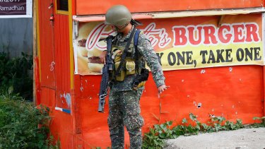 A Philippine marine signals his men to slow down as they near a corner at the frontline in Marawi city on Sunday.