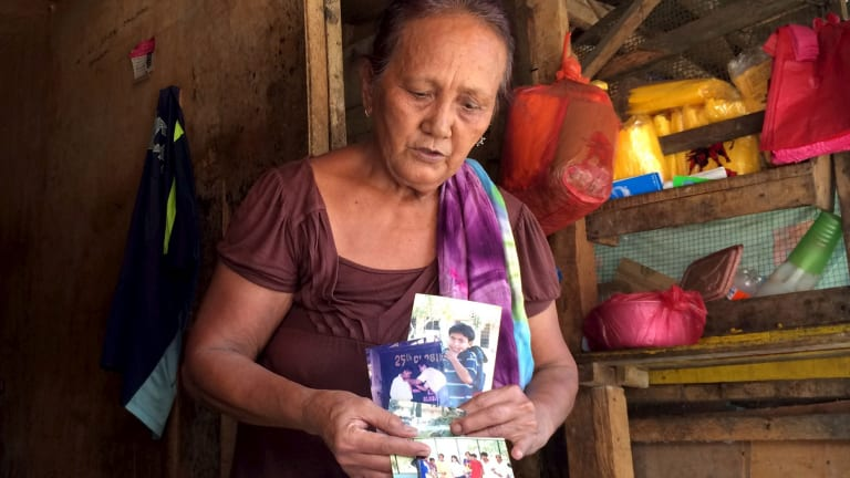 Clarita Alia, 62, in Davao, holds up photographs of four teenage sons killed by vigilantes - she blames Philippine president elect, Rodrigo Duterte.