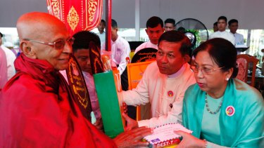 General Min Aung Hlaing and his wife Daw Kyu Kyu Hla offer alms to Buddhist monks earlier this month.