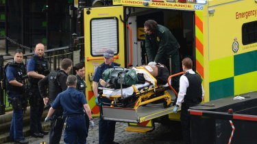 An attacker is treated by emergency services outside the Houses of Parliament in London.