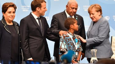 German Chancellor Angela Merkel, right, talks to Fiji prime minister and COP president Frank Bainimarama, second right, and Timoci Naulusala, a child from Fiji, with Patricia Espinosa, executive secretary of the United Nations Framework Convention on Climate Change, left, and French President Emmanuel Macron.