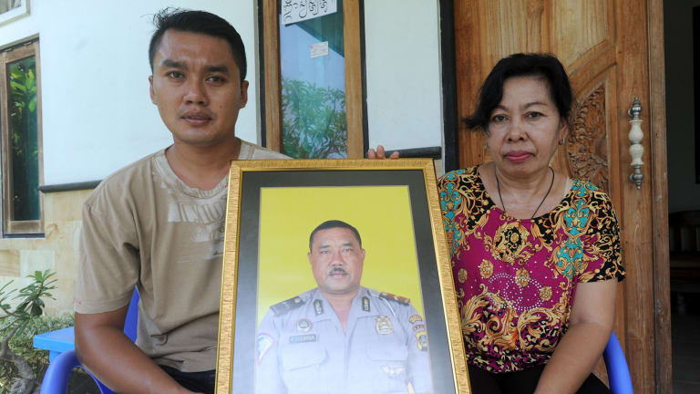 The widow of Wayan Sudarsa, Ketut Arsini, and her son Kadek Toni, hold a portrait of the police officer who was killed on Legian beach.