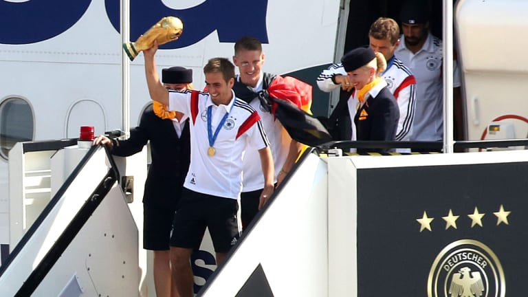 Home with the big prize: German captain Phillipp Lahm steps off the team plane in Berlin in Tuesday.