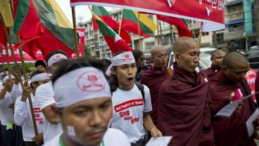 "Nationalists wearing T-shirts that say ""Stop Blaming Myanmar"" and ""Boat People are not Myanmar"" and Buddhist monks march in a protest rally in Yangon."