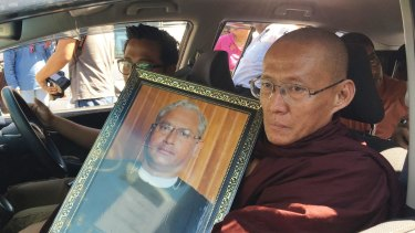 A Buddhist monk holds a portrait of Ko Ni, who spoke out about how the constitution stacked power in the hands of the military and was inconsistent with democracy.