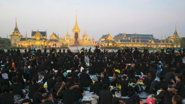 Thai mourners sits in front of the Royal Crematorium and funeral complex ahead of King Bhumibol cremation.