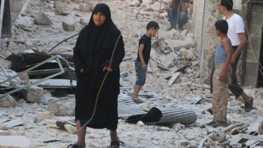 Civilians walk on rubble as they inspect a site hit by what activists said was a barrel bomb dropped by forces loyal to Syria's President Bashar al-Assad in the old city of Aleppo on July 12.