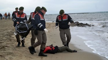 Turkish paramilitary police officers collect the body of a refugee lying on the beach in Ayvalik. 35 bodies have been found by authorities after the latest boat disaster.