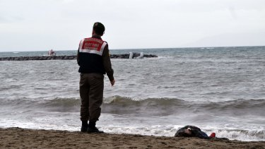 A Turkish paramilitary police officer stands next to the body of a refugee lying on the beach in Ayvalik, Turkey.