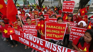 Filipinos and Vietnamese expatriates display placards during a rally at the Chinese Consulate to protest China's South China Sea activities.