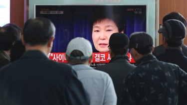 People watch a TV screen showing the live broadcast of South Korean President Park Geun-hye in Seoul on Friday.