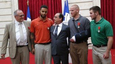French President Francois Hollande (centre) poses with (from left) British businessman Chris Norman,  Anthony Sadler, Spencer Stone and Alek Skarlatos.