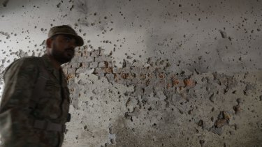 A Pakistani army soldier walks past a bullet-riddled wall.