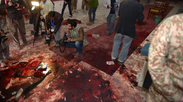 Pakistan media take footage of the bloodied floor at an army-run school a day after an attack by Taliban militants in Peshawar.