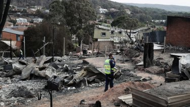 A police officer takes photos of the aftermath of the Tathra bushfires, which destroyed 68 homes.