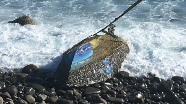 The upturned boat being hauled from Cascade Bay.