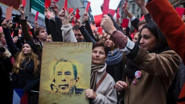 The Czechs have long memories of Russian domination. A woman holds a placard with a picture of former president of Vaclav Havel on the 25th anniversary of the Velvet Revolution.