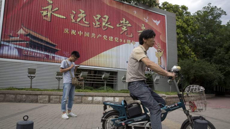 A man smokes near a billboard with the words 'Always follow the Communist Party' to mark the 94 anniversary of the founding of the Communist Party of China in Beijing.