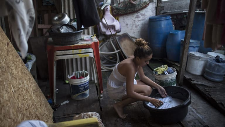 Marilia da Silva, 14, washes her clothes in a slum in Recife, Brazil. The Zika virus, spread by the Aedes aegypti mosquito which also spreads dengue, thrives in people's homes and can breed in even a bottle cap's-worth of stagnant water.