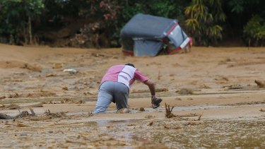 An man stuck in the mud after a landslide in Elangipitiya village.