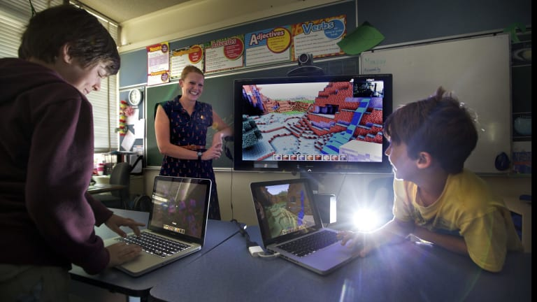"Switched on: North Fitzroy Primary School teacher Rebecca Martin has embraced gaming technology in her class. Students Eamon, left, and Hemi, enjoy building worlds in ""Minecraft""."