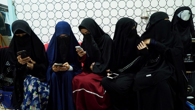 Women wearing niqabs chat at the home of a founder of the Niqab Squad in Bogor, Indonesia.