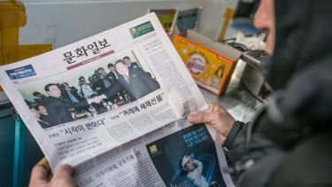A man looks at a newspaper featuring a photograph of the meeting.