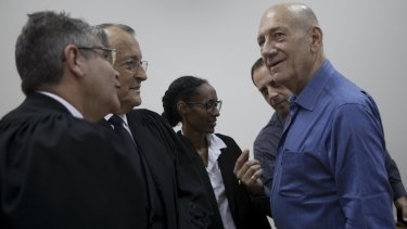 Ehud Olmert with his lawyers on Monday.