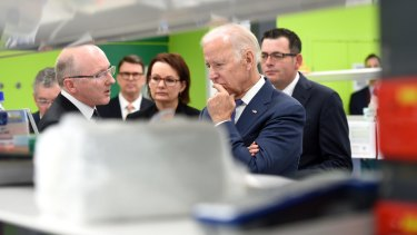 Professor Sean Grimmond, who investigates ovarian and pnacreatic cancer genomes, shows Health Minister Susan Ley, US Vice President Joe Biden and  Victorian Premier Daniel Andrews around a research labs at the Victorian Comprehensive Cancer Centre.