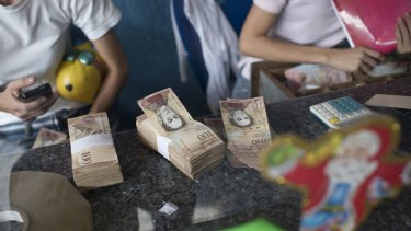 Employees organise 100-bolivar notes at a lottery store in Caracas, Venezuela, on Monday.