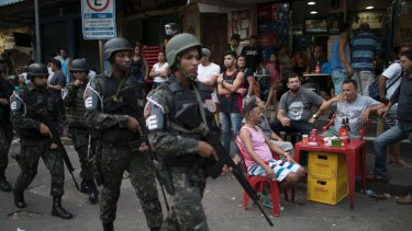 Soldiers walk past men drinking beer during an operation in the Rocinha slum of Rio de Janeiro on Friday.