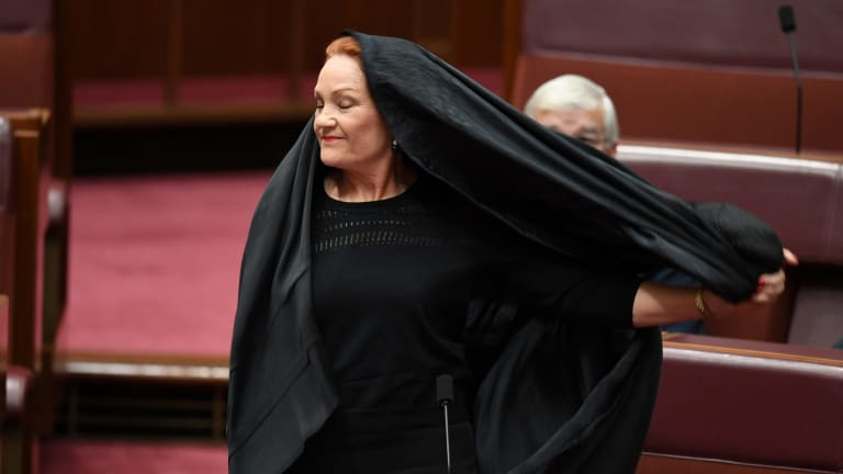 One Nation Senator Pauline Hanson takes off a burqa during Senate Question Time at Parliament House in Canberra in August.