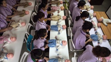 Chinese women train on dolls to become qualified nannies at the Ayi University in Beijing.
