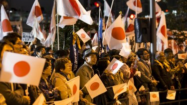 People wave Japanese national flags in support of Shinzo Abe during a campaign rally in Tokyo, on Saturday.