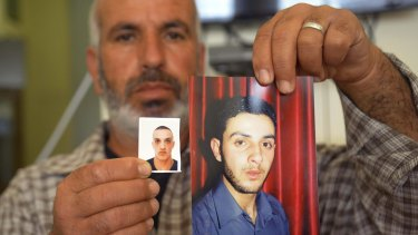 A relative with photos of the Har Nof synagogue attackers, Ghassan (right) and Uday Abu Jamal, outside the family home in Jerusalem.