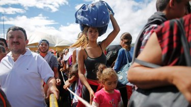 A woman carrying a bundle on her head waits in line to cross the border into Colombia through the Simon Bolivar International Bridge in San Antonio del Tachira, Venezuela.